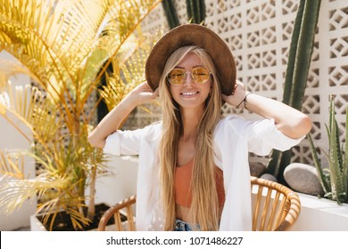 Emotional girl with blonde straight hair posing with eyes closed in resort restaurant. Outdoor photo of charming caucasian female model in brown hat smiling during photoshoot in cafe.
