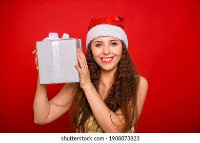Emotional girl in a Christmas hat with a gift in her hands posing isolated on a red background.