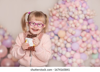 An emotional girl with down syndrome eats a chocolate bar. Against the background of balloons. Delicate light colors