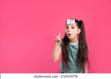 Emotional girl with question mark sticker on forehead against pink background. Space for text