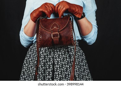 Emotional Girl in retro style with leather gloves and purse on a black background