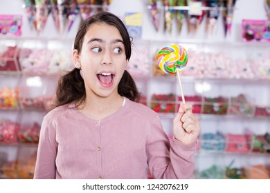 Emotional girl standing with  sweet colored lolly  on stick in candy shop
