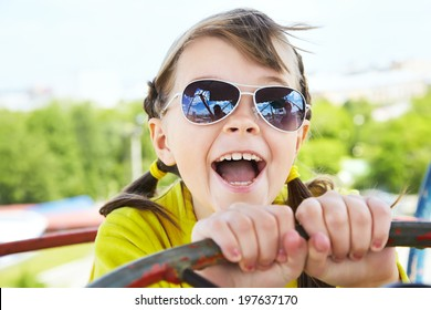 emotional girl in sunglasses in the amusement park. children outdoors. vacation in the summer park