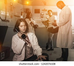 Emotional girl using telephone set while trying to get out with friends of escape room stylized as underground shelter
