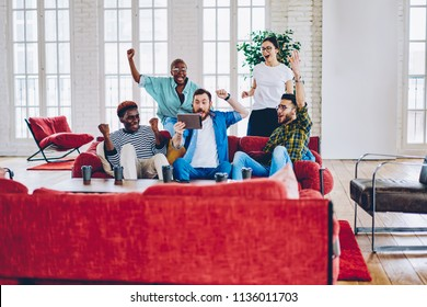 Emotional group of male and female friends cheering for favorite team surprise with  victory watching online on digital tablet, hipsters screaming excited with results of match read on touchpad