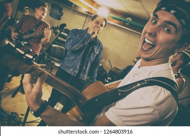 Emotional guitarist on repetition with rock band in garage. Funny musician looking at camera, showing tongue with opened mouth. Members of group practicing, singing and playing guitar.