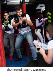 Emotional guy with laser pistol playing laser tag with friends on dark labyrinth