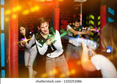 Emotional guy playing laser tag with friends on dark labyrinth in colorful beams of laser pistols