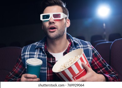 emotional handsome man in 3d glasses with popcorn and soda watching movie in cinema