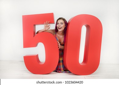 Emotional and happy beautiful young woman looks into the camera while sitting on the floor between the big red numbers five and zero, showing a gesture that everyone is well. Final sale. 50% discount.