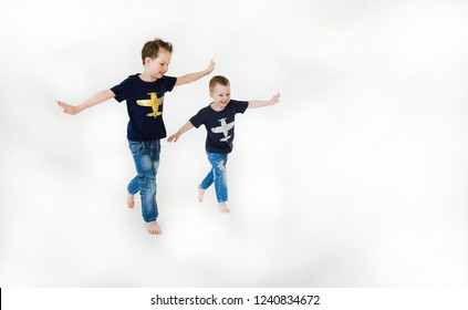 Emotional and happy little brothers running around each other and holding hands in the form of aircraft wings in a bright game room. Happy childhood. Portrait of happiness. Lifestyle. Positive