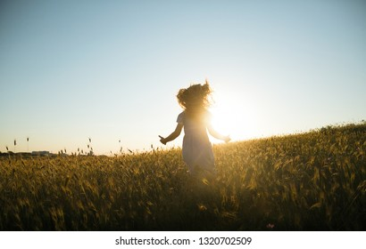 Emotional and happy little girl running across a wheat field to the sunset side against the sky. Summertime . Summer vacation. Lifestyle. Happy childhood. Positive emotions and energy.