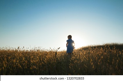 Emotional and happy little girl running across a wheat field to the sunset side against the sky. Lifestyle. Summertime. Summer vacation in nature. Positive emotions and energy. Happy childhood