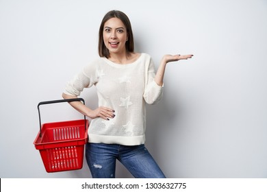 Emotional happy woman holding empty shopping basket and showing copy space on the open hand palm, looking at camera