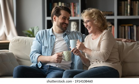 Emotional happy young handsome man telling funny joke or story to laughing middle aged 60s mother, relaxing on comfortable couch with cups of tea, family communication trustful relations concept.