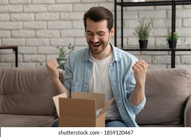 Emotional happy young man in eyeglasses opening small cardboard parcel, celebrating getting wished item, satisfied with shopping experience in online store or fast delivery service, getting gift.