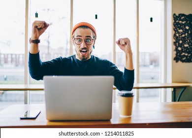 Emotional hipster guy celebrating victory in competition raising hand and screaming sitting near laptop computer, overjoyed male student wondering of winning online. Achievement in business goal