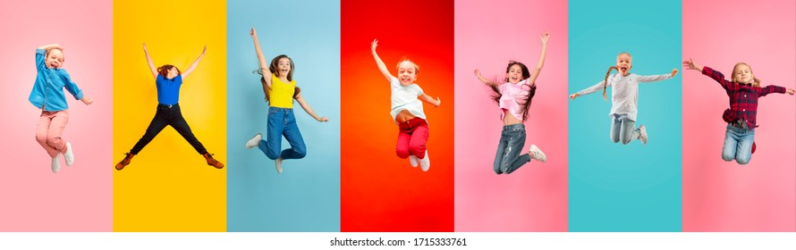 Emotional kids and teens jumping high, look happy, cheerful on multicolored background. Delighted, winning girls. Emotions, facial expression concept. Trendy colors. Creative collage made of 5 models