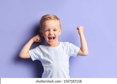 Emotional little boy full of happy feelings. Portrait, isolated over purple background
