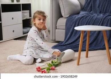 Emotional little girl and broken ceramic vase on floor at home