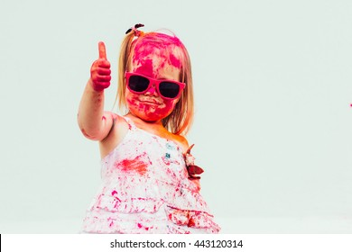 Emotional little girl in pink sun-glasses with colors of Holi . Bright summer colors and cheerful little girl