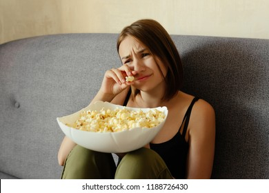 Emotional lovely girl crying while watching a drama movie, eating popcorn, at home.