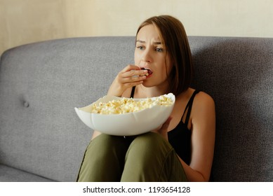 Emotional lovely girl watching a drama movie, eating popcorn, at home.