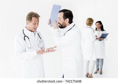 emotional male doctors talking while female colleagues standing behind, isolated on white