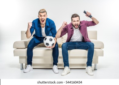 Emotional male friends sitting on couch with soccer ball and supporting favorite team isolated on white