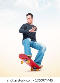 Emotional man in casual clothes performs a trick on a skateboard, on light background.