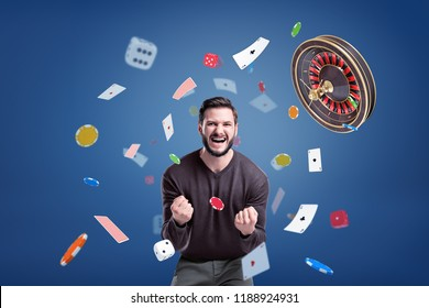 An emotional man cries angrily at camera, surrounded by a flying roulette, chips, cards and dice. Loss or gain. Strong gambling emotions. Big prize for winner.
