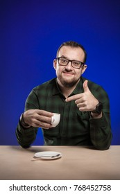 Emotional man in glasses is drinking coffee from a white cup at the table with a laptop and phone, and posing on a blue background