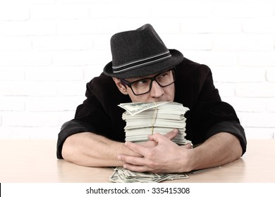 emotional man in glasses holding bundles of money