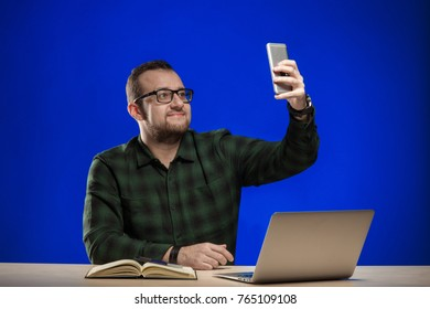 Emotional man in glasses sits at a table with a laptop, holds a phone in hands, posing on a blue background