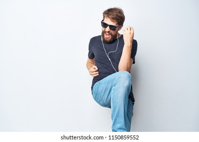emotional man with glasses and white headphones dancing on a light background
