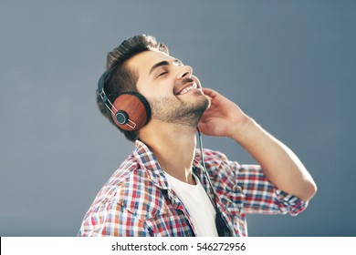Emotional man with headphones listening music on grey background