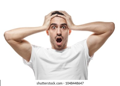 Emotional man isolated on white background with strong expression of fear, round eyes, open mouth and hands pressed to top of head, showing astonishment and shock