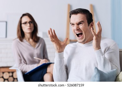 Emotional man screaming while consulting with psychologist