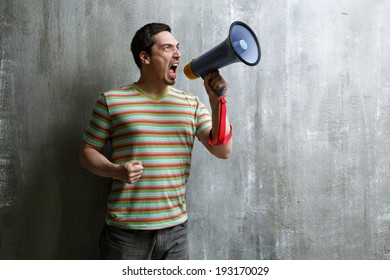 Emotional man shouts through a megaphone on a background of gray wall texture.