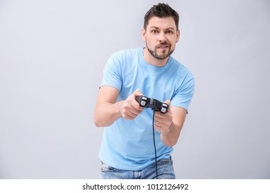 Emotional man with video game controller on grey background