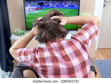 Emotional man watches football in TV. The unhappy disappointed football fan looks at soccer in television at home.