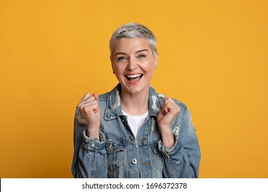 Emotional mature woman shouting and celebrating success with clenched fists, feeling excited, posing over yellow studio background, copy space