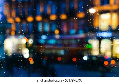 Emotional melancholic abstract background with defocused lights bokeh in London, UK behind rain drops in window glass, Focus on few drops due to the shallow depth of field