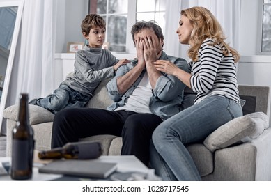 Emotional moment. Emotional depressed alcoholic man sitting at home and hiding his face while his kind understanding supporting family members sitting by near and looking at him