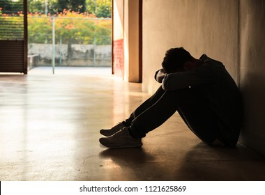 Emotional moment: man lowers head and arms on his knees, stressed sad young male having mental problems, feeling bad, depressed, disappointed, hopeless. Desperate man in dark corner need help and care