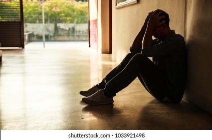 Emotional moment: man sitting holding head in hands, stressed sad young male having mental problems, feeling bad, depressed, disappointed, hopeless. Desperate man in dark corner needing care and help.