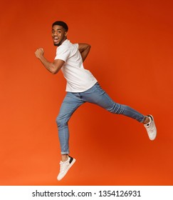 Emotional motivated african-american man running to aim on air, jumping on orange background