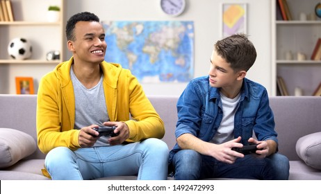 Emotional multiracial male teen friends playing video game, hobby and rivalry