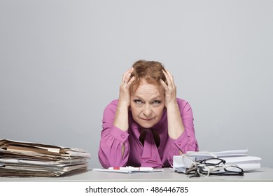 Emotional Old woman at the table with documents