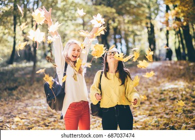 Emotional photo of two girls student with happy joyful emotions throwing yellow leaves in the air in sunny autumn park. Education, lifestyle and people concept.